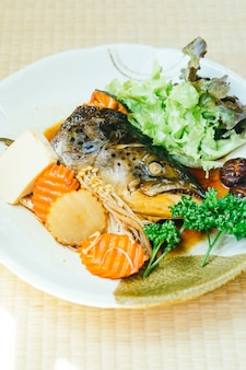Cabeça cozida de peixe salmão com molho doce e vegetal
