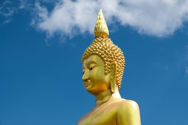 Cabeça da estátua de buda de ouro contra o céu azul e nuvens