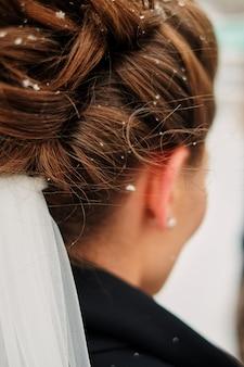 Cabeça da noiva em flocos de neve. flocos de neve no cabelo da menina. fechar-se