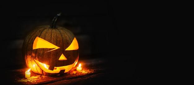 Cabeça de abóbora de halloween com velas em chamas