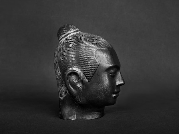 Cabeça de buda, cor preta esculpida em pedra na parede escura. o rosto do antigo buda de pedra, vista lateral.