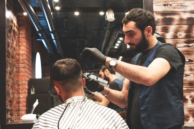 Cabeça de corte de cabelo na barbearia. o barbeiro corta o cabelo na cabeça do cliente. o processo de criação de penteados para homens. barbearia. foco seletivo.