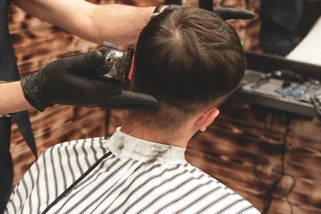 Cabeça de corte de cabelo na barbearia. o barbeiro corta o cabelo na cabeça do cliente. o processo de criação de penteados para homens. barbearia.