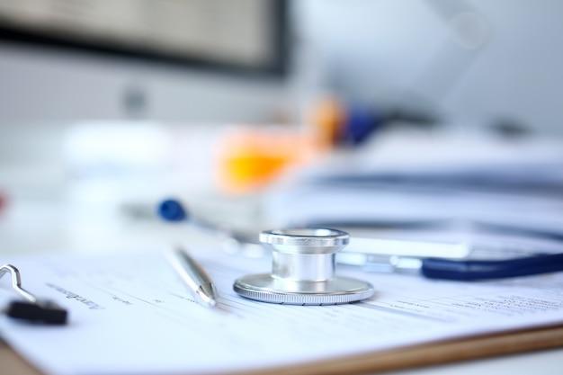Cabeça de estetoscópio e caneta prata, deitado no formulário de candidatura médica