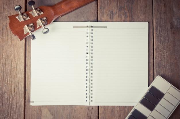 Cabeça de guitarra e mini-chave em um livro para escrever músicas