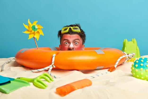 Cabeça de jovem com protetor solar no rosto e acessórios de praia