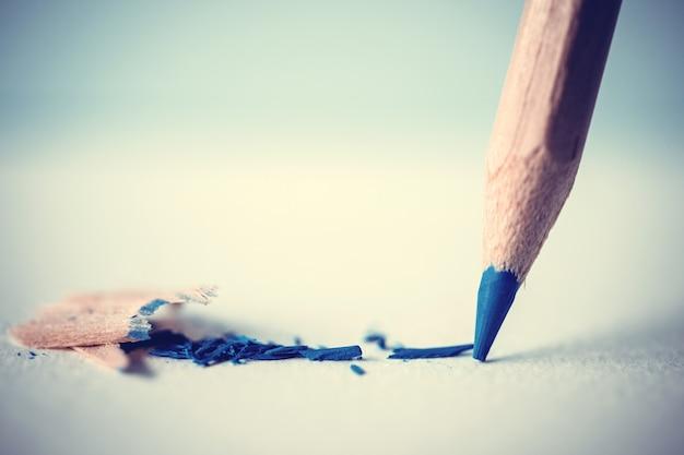 Cabeça de lápis de cor azul no papel de desenho branco