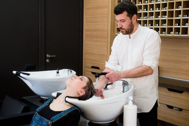 Cabeça de lavagem de cabeleireiro para a jovem mulher no cabeleireiro