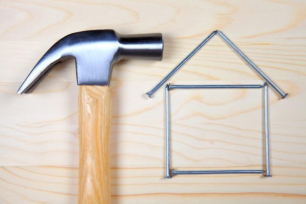 Cabeça de martelo e casa de pregos em fundo de madeira