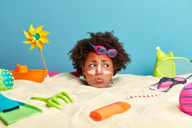 Cabeça de mulher jovem com protetor solar no rosto e acessórios de praia