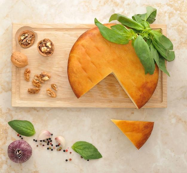Cabeça de queijo suluguni defumado na placa de madeira com nozes e manjericão na superfície de mármore