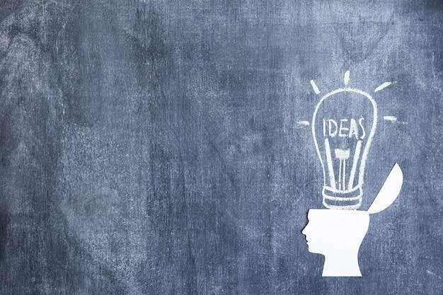 Cabeça de recorte de papel branco aberto sobre a lâmpada de idéias desenhadas no quadro-negro