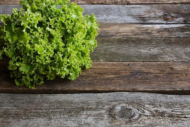 Cabeça de salada fresca verde com raiz na superfície de madeira áspera velha, conceito de alimentação saudável, foco seletivo