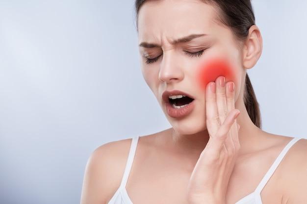 Cabeça e ombros de menina com expressão de rosto dolorido, segurando a mão na bochecha, dor de dente. paciente com os olhos fechados sofrendo de dor de dente, conceito estomatológico