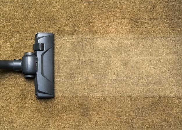 Cabeça escura de um aspirador de pó moderno sendo usado para aspirar um tapete.