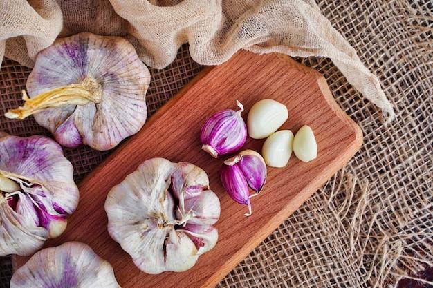 Cabeça fresca de alho e cravo-da-índia em uma placa de madeira em um conceito de produtos ecológicos de estilo rústico