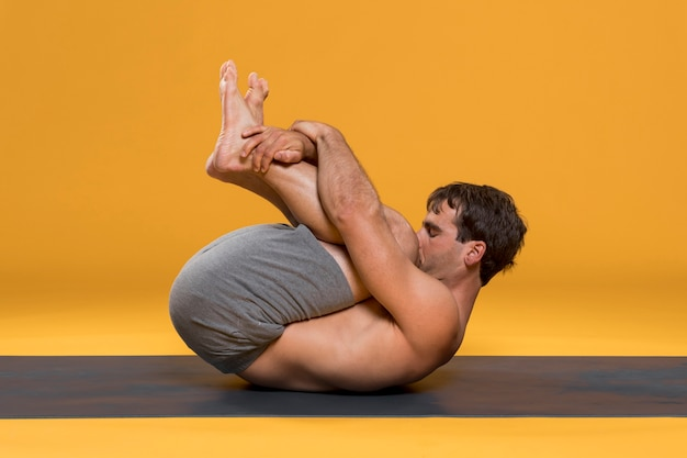 Cabeça para os joelhos posar no tapete de yoga