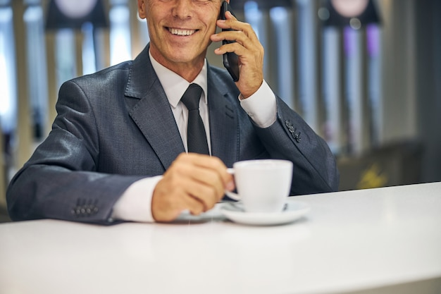 Cabeça recortada de um homem alegre e elegante desfrutando de uma xícara de café enquanto fala ao celular