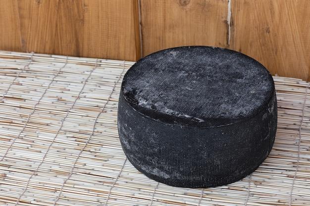 Cabeça redonda inteira de queijo duro parmesão ou parmigiano na madeira