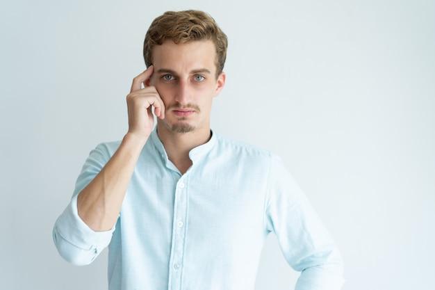 Cabeça tocante do homem novo pensativo com dedo e vista da câmera.