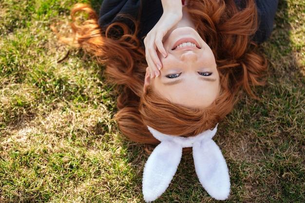 Cabeça vermelha mulher usando orelhas de coelho de páscoa ao ar livre