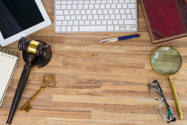 Cabeçalho de herói do espaço de trabalho com gawel de lei, livro jurídico e teclado de laptop, vista superior, espaço de cópia na mesa de madeira