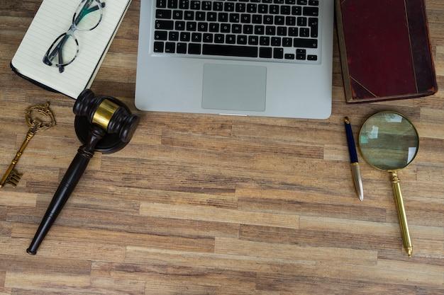 Cabeçalho de herói do espaço de trabalho com gawel de lei, livro jurídico e teclado de laptop, vista superior, espaço de cópia no fundo da mesa de madeira