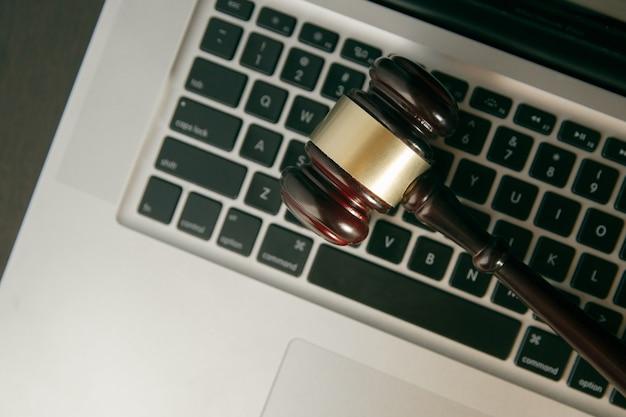 Cabeçalho do herói do espaço de trabalho com martelo de lei. conceito de leilão online. martelo de leilão ou juiz em um teclado de computador. martelo de lei.