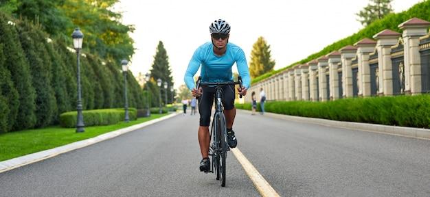 Cabeçalho do site da foto recortada de um homem andando de bicicleta de montanha no parque durante o pôr do sol
