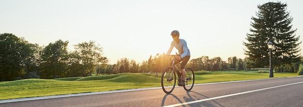 Cabeçalho do site da vista traseira de um homem atlético em roupas esportivas em pé com uma bicicleta no