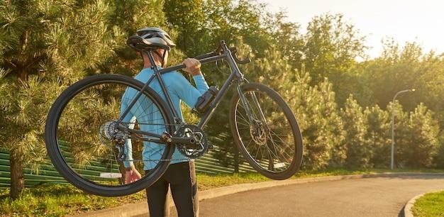 Cabeçalho do site de um homem forte e atlético em roupas esportivas segurando uma bicicleta enquanto está em um parque