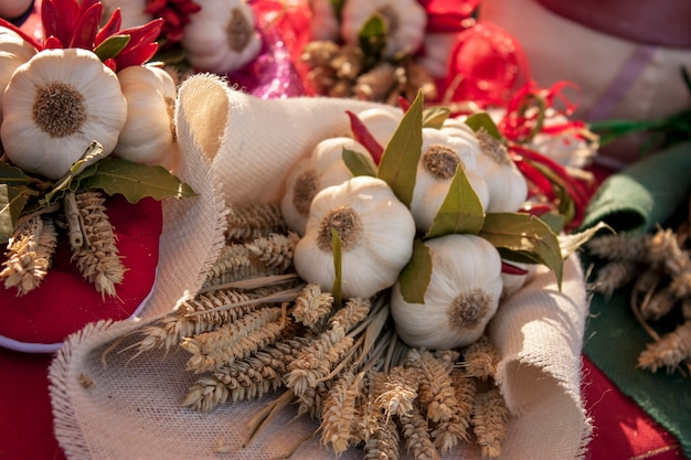 Cabeças de alho e trigo e pimenta em uma composição decorativa com alimentos para embelezar uma barraca de um mercado de frutas e vegetais.