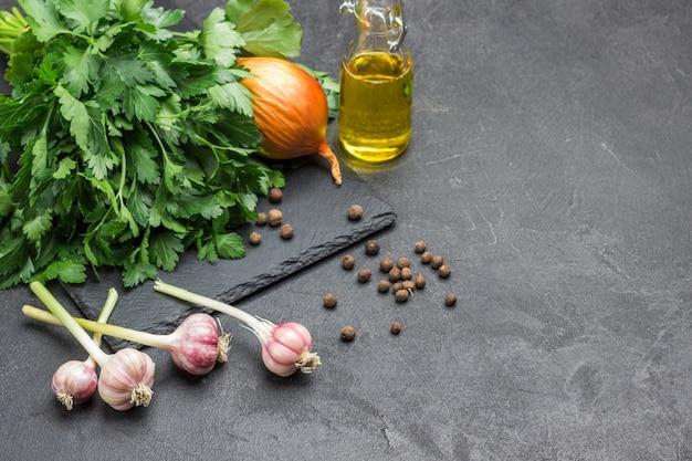 Cabeças de alho, pimenta da jamaica, óleo e ramo de salsa no preto. fundo vegetal. copie o espaço. vista do topo.