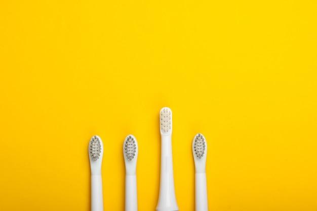 Cabeças de escova de dentes em uma superfície amarela