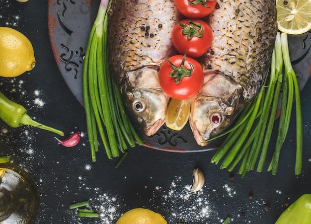 Cabeças de peixe cru no prato decorativo com legumes