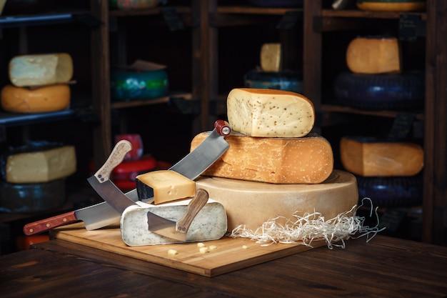 Cabeças de queijo com fatias e facas em uma placa de madeira com um interior