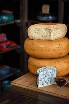 Cabeças de queijo com fatias em uma placa de madeira com um interior