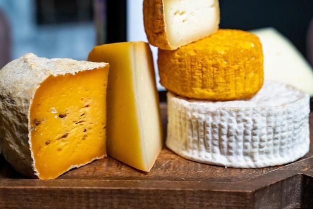 Cabeças de queijo sortidas em uma placa de corte em uma mesa de madeira. fábrica de queijos e loja de queijos. produtos lácteos naturais da fazenda. publicidade e menus.