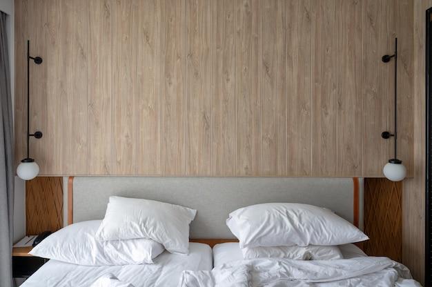 Cabeceira de madeira com abajur de quarto com travesseiro amassado e cobertor