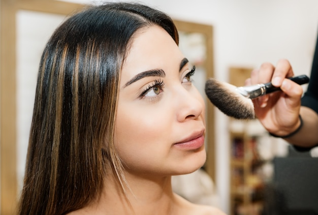 Cabeleireira maquiando uma linda garota caucasiana de cabelos longos e grandes olhos verdes e muito bonita