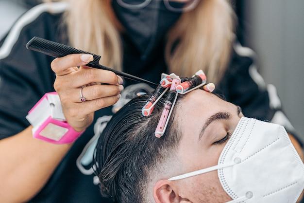 Cabeleireiro ajeitando os cachos do cabelo de um jovem caucasiano com máscara usando o alfinete de um pente