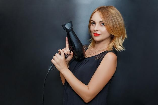 Cabeleireiro alegre, mulher posando com um secador de cabelo nas mãos dela
