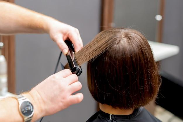 Cabeleireiro alisa o cabelo da mulher