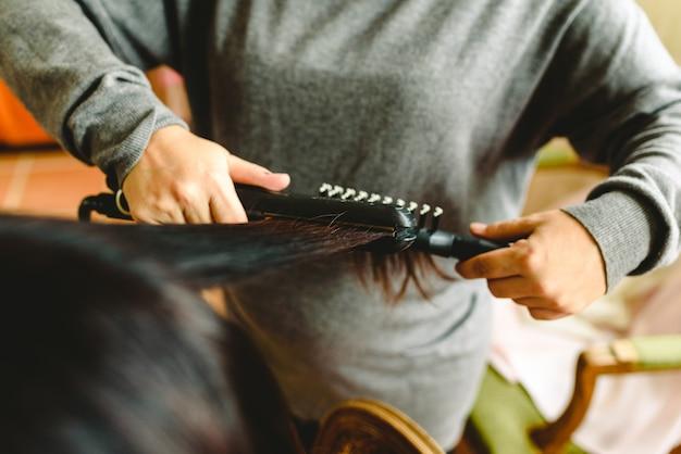 Cabeleireiro alisando o cabelo escuro de um cliente.