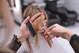 Cabeleireiro anónimo cortando o cabelo do cliente