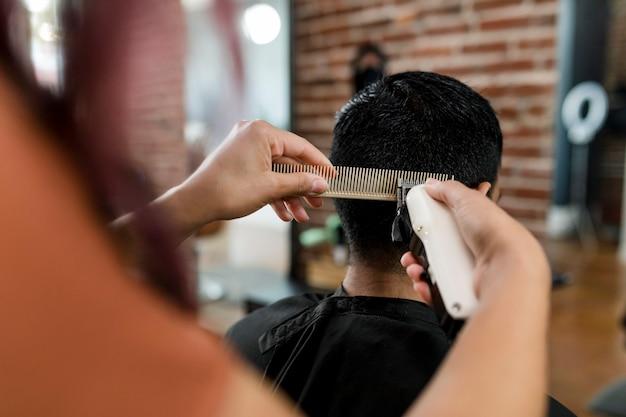 Cabeleireiro aparando o cabelo da cliente em uma barbearia