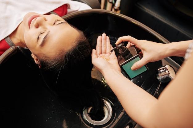 Cabeleireiro apertando shampoo na mão