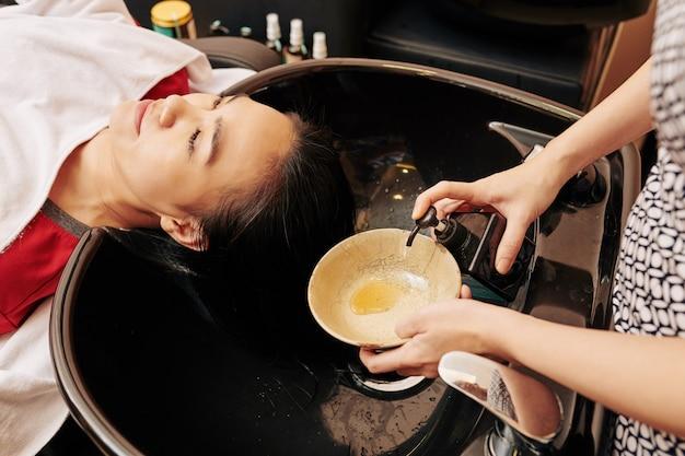 Cabeleireiro apertando shampoo