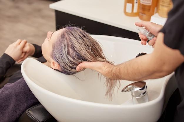 Cabeleireiro aplicando soro capilar no cabelo da cliente após tingimento e tonificação