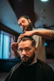 Cabeleireiro barbudo fazendo penteado masculino moderno